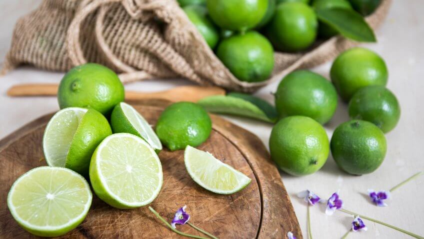 Lime citrus fruit on wooden board.