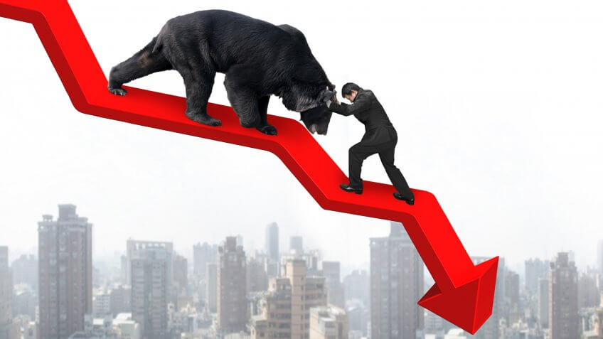 Businessman against black bear on red arrow downward trend line with sky cityscape background.