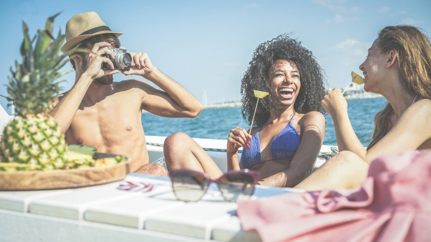 Happy friends having fun and eating fresh pineapple fruit at boat party - Young people taking photos in caribbean sea tour - Youth, tropical, travel and summer vacation concept - Focus on black girl.