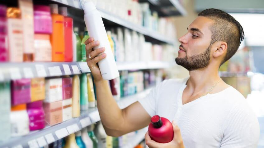 Attractive man buying shampoo in shopping mall.