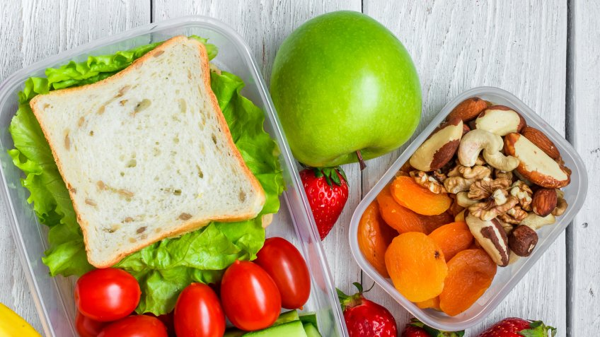 school lunch boxes with sandwich and fresh vegetables, bottle of water, nuts and fruits on white wooden background.