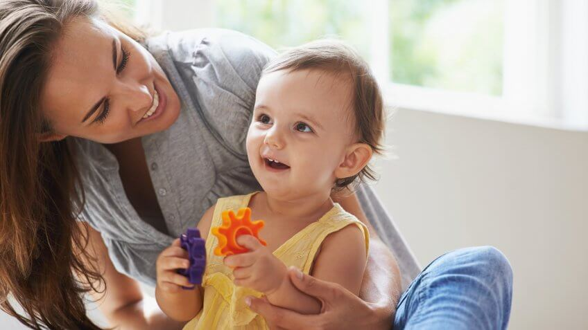 Shot of a cute baby girl sitting on the floor with her mom and playing with toys.