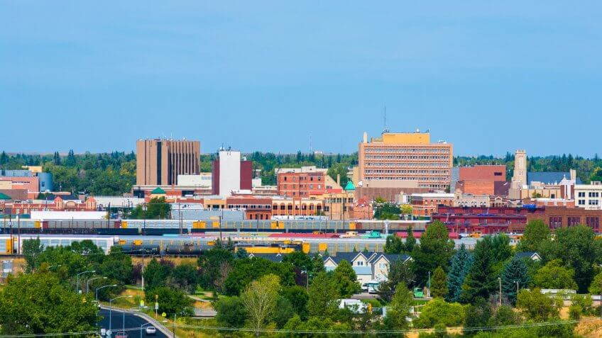 Cheyenne downtown skyline with train cars, houses, and trees in view.
