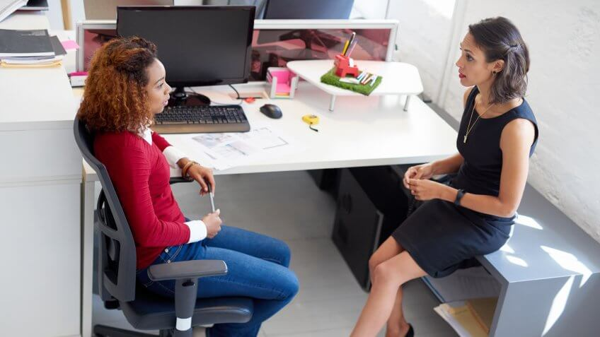 two colleagues talking at a desk in an office