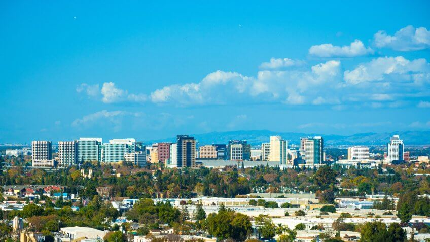 Vista of the San Jose skyline, with puffy clouds in the background and residential areas in the foreground.