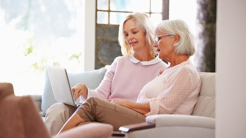Daughter Helping Senior Mother With Computer At Home