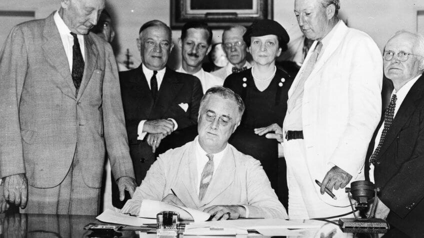 Roosevelt signs Social Security Bill.