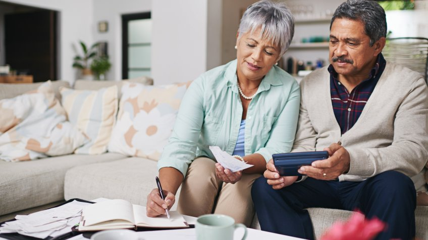 elderly couple working out a budget while sitting on the living room sofa