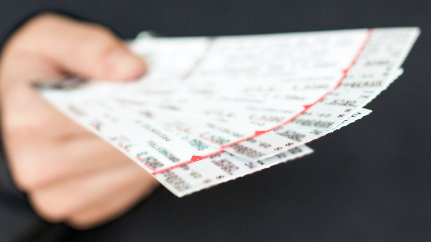 Tickets to a show / event in a hand with a black background.