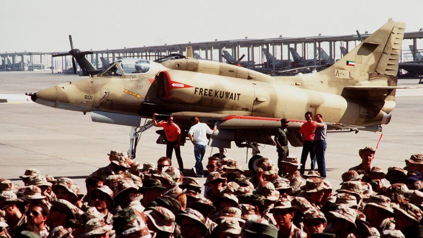 A Kuwaiti A-4KU Skyhawk aircraft sits parked on the fringes of a crowd that has gathered to listen to a speech by President George Bush.