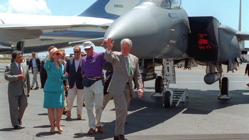 President William Jefferson Clinton and the First Lady wave as they walk across the runway for the commemoration of the 50th anniversary of the end of World War II.