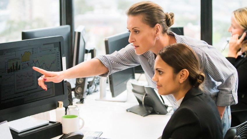 Businesswomen working together at computer workstation.