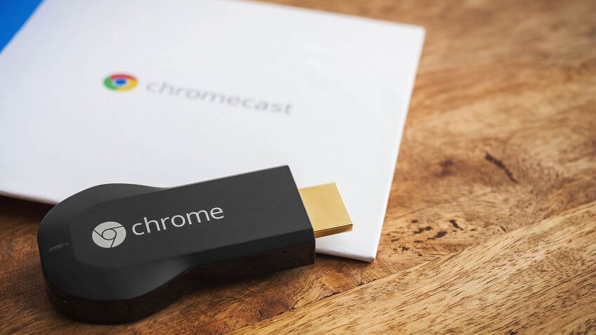 VIENNA, AUSTRIA, 10 May 2014: Google Chromecast HDMI-Dongle on a wooden surface with parts of its original packaging.