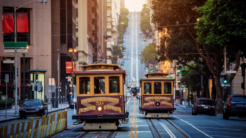 Classic view of historic traditional Cable Cars riding on famous California Street in morning light at sunrise with retro vintage style cross processing filter effect, San Francisco, California, USA.