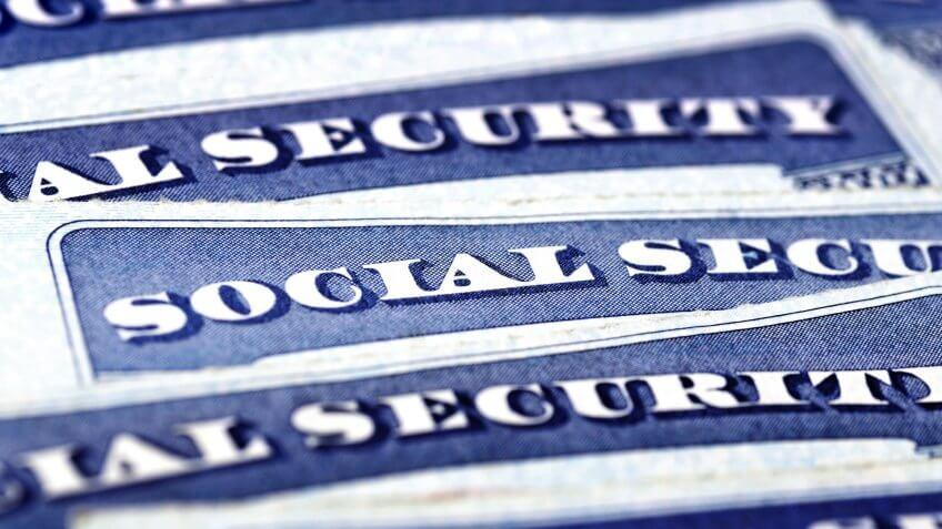 Closeup detail of several Social Security Cards representing finances and retirement.