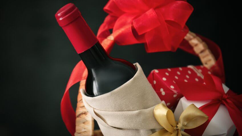 Wine bottle with gift boxes in wicker basket on dark background.