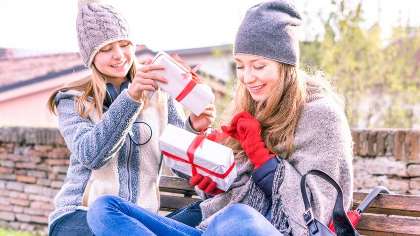Happy women holding gifts box in winter clothing outdoors at city park - Young sisters opening presents sitting on urban bench with smiling face - Love and teenage friendship concept.