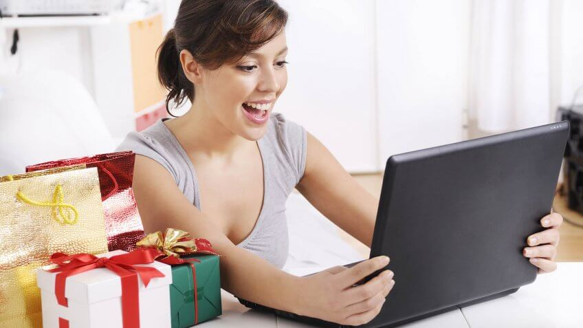 happy shopping on-line of young woman with laptop on internet.