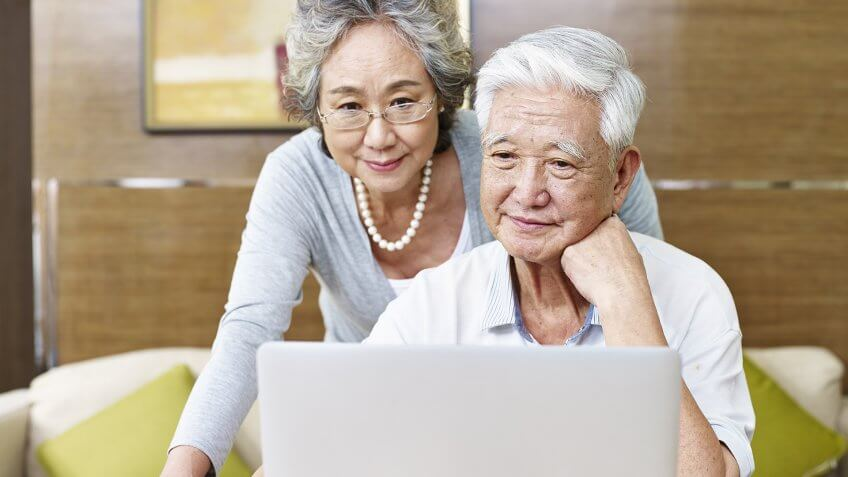 loving senior asian couple using a laptop computer together.