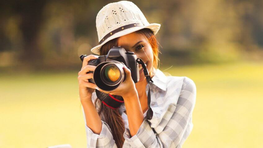 smiling young woman using a camera to take photo outdoors at the park.