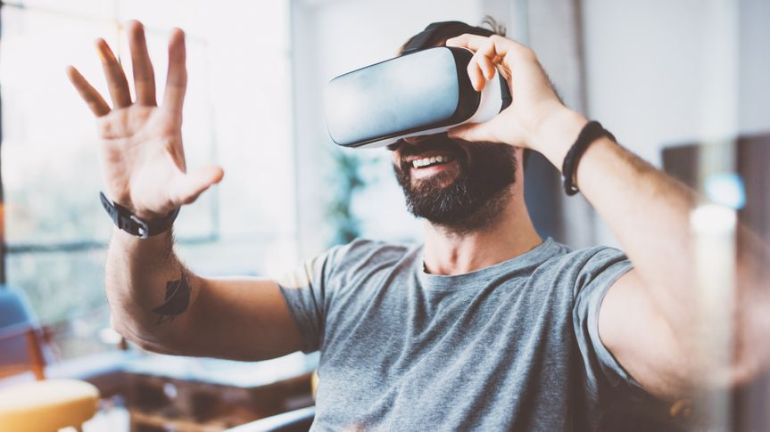 Young bearded man wearing virtual reality glasses in modern interior design coworking studio.