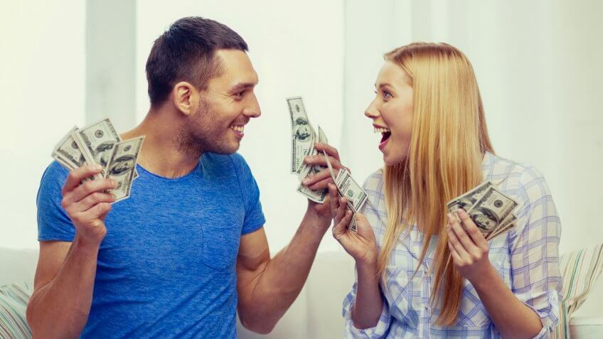 love, family, finance, money and happiness concpet - smiling couple with money and piggybank ot table at home.