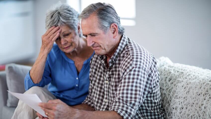 Worried senior couple checking the bills at home.