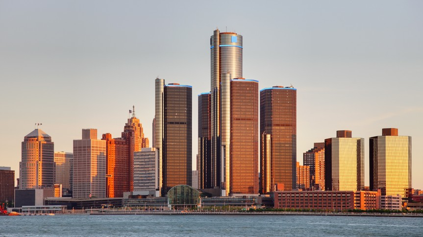 Detroit city skyline along the Detroit River at dusk.
