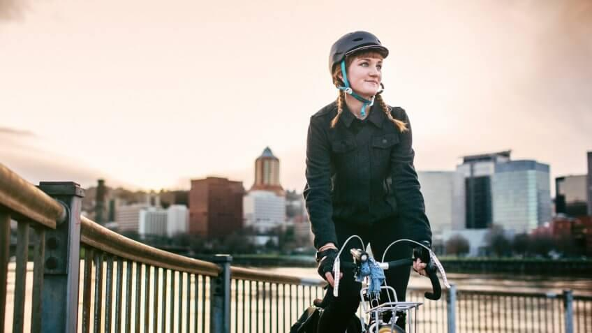 A smiling young woman commuting in an urban city environment on her street bicycle, waterproof panniers on her bike rack.