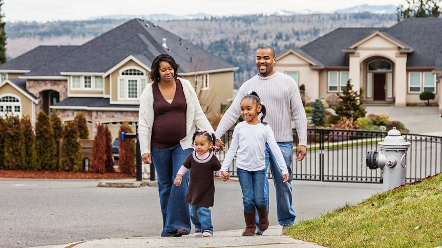 Photo of a young African American family taking a walk in the neighborhood, mother 8 months pregnant.