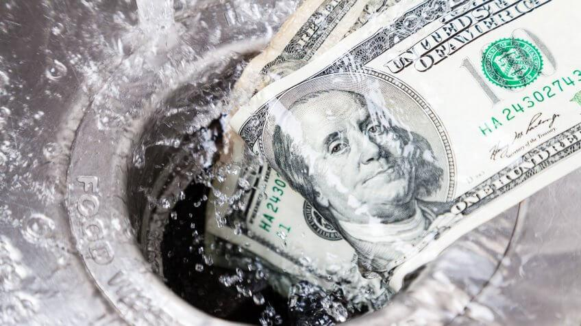 $100 dollar bill being washed down garbage disposal