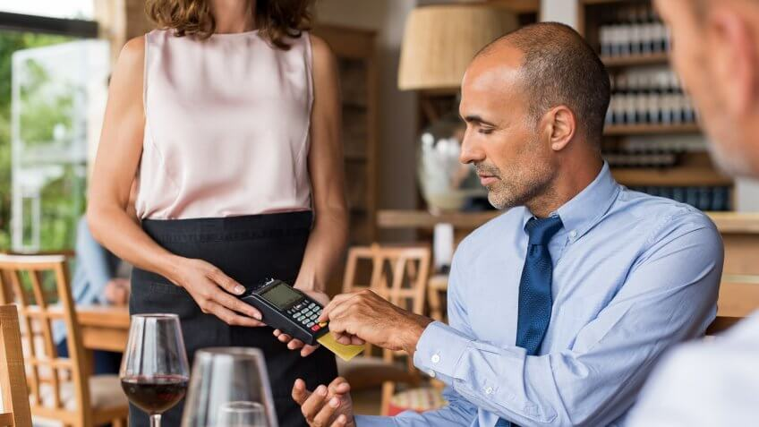 Waiter holding credit card swipe machine while customer typing code.