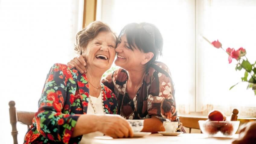 Senior Woman Enjoying a relaxing moment with her Daughter at Home drinking Coffee.