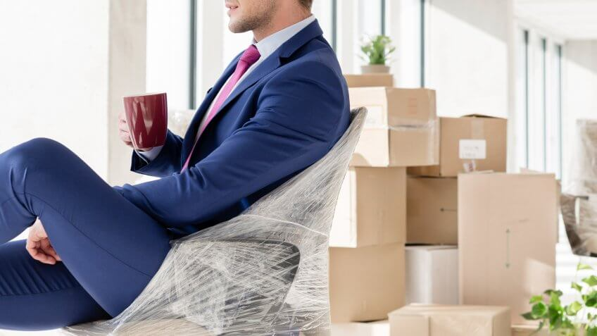Businessman in office with moving boxes
