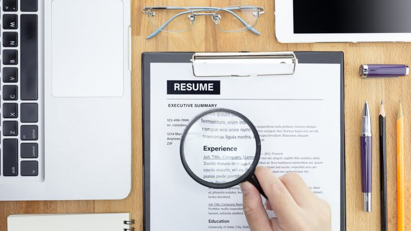 looking at resume with magnifying glass