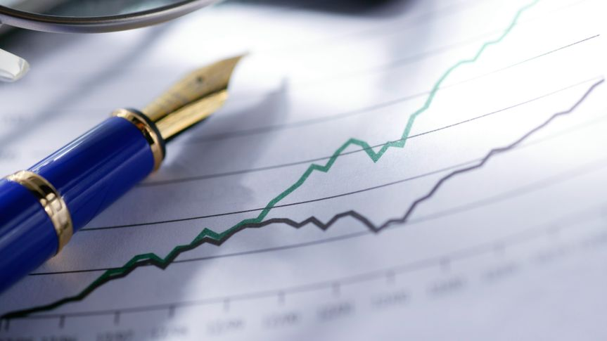 A blue and gold fountain pen and a pair of eyeglasses sit on top of a chart showing diverging trend in sales growth or stock market performance.