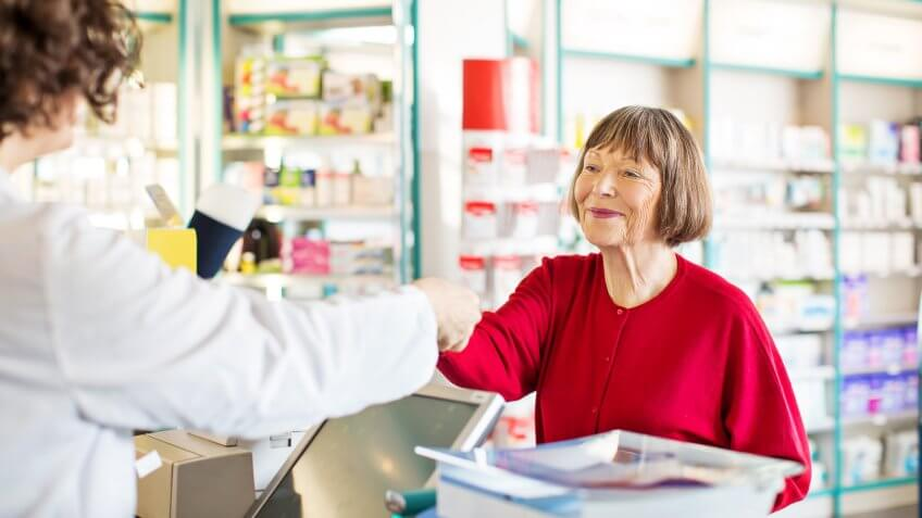 customer standing at chemist counter as pharmacist hands her medication order