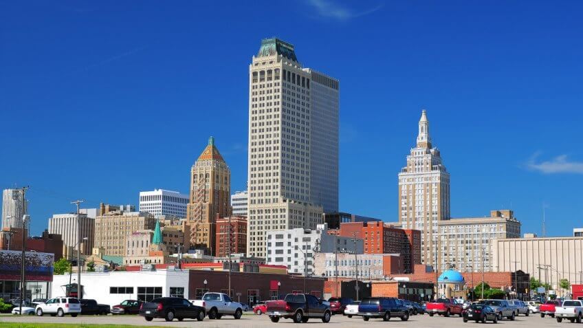 """A view of Tulsa downtown buildings, including three historic buildings and two skyscrapers, with a parking lot and cars in the foreground."