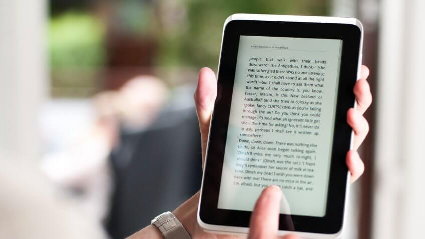 Left hand is holding a tablet or ereader with a digital version of the novel Alice's Adventures In Wonderland by Lewis Carroll.