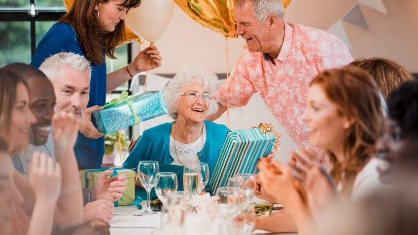 Senior woman is overwhelmed with emotion as she is surprised with a birthday party