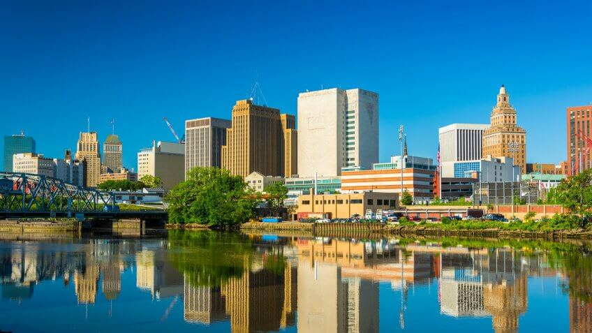Newark downtown skyline with a mirror like reflection on the Passaic River in the foreground.