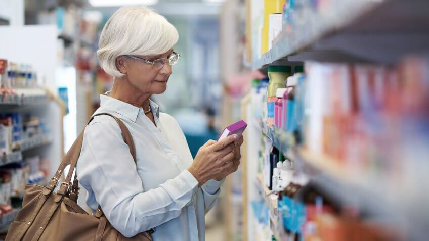 elderly woman looking at products in a pharmacy
