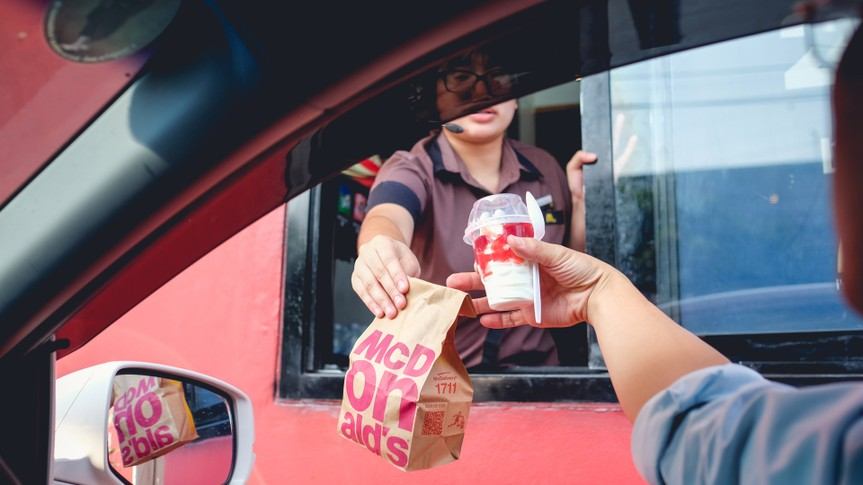 Bangkok, Thailand - Mar 4, 2017: Unidentified customer receiving hamburger and ice cream after order and buy it from McDonald's drive thru service, McDonald's is an American fast food restaurant chain.