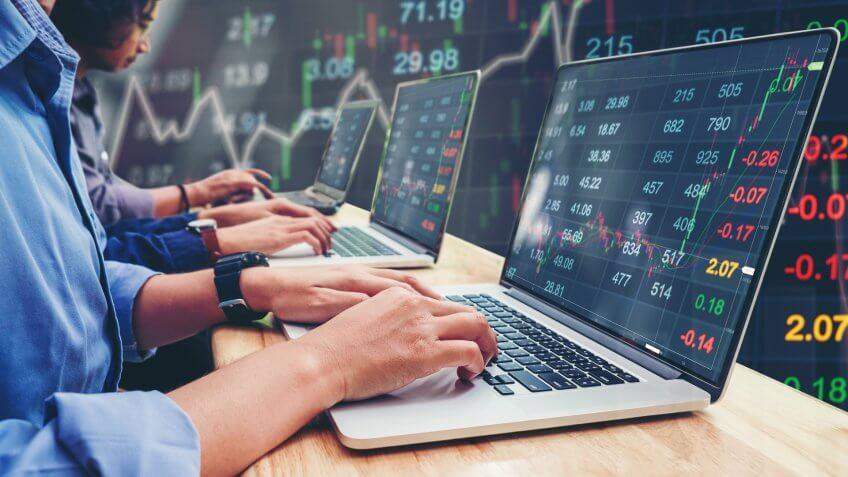 team of investors looking at stocks
