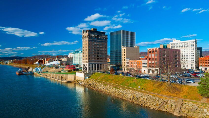 Charleston, West Virginia skyline with the Kanawha River in the foreground and a blue sky with clouds.