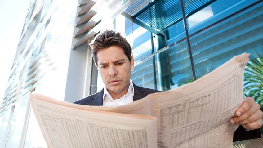 businessman reading stock newspaper