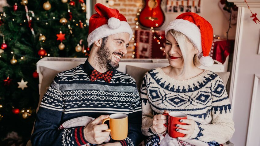 Couple relaxing and drinking tea in front of a Christmas tree.