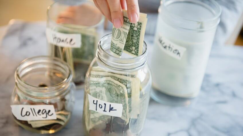 Woman saving money in jars.