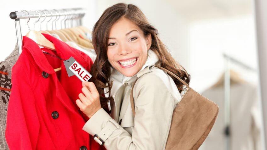 Shopping woman excited showing price tag at clothes sale in clothing store.