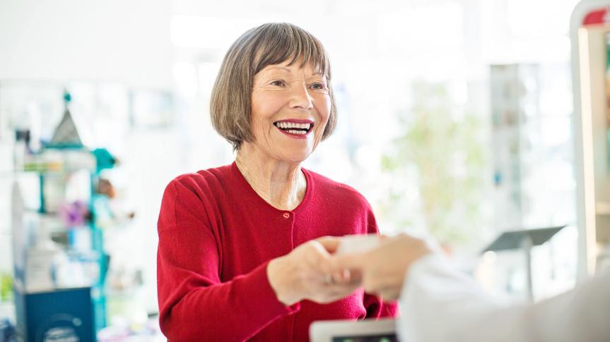 Happy female customer taking medicine from pharmacist at pharmacy.